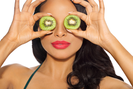 tanned girl: Fun portrait of a tanned girl holding two green kiwi slices with bright pink lipstick. Stock Photo