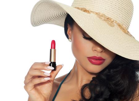 kapelusze: Piękne kobiety w kapeluszu letni stwarzające z czerwoną szminką.