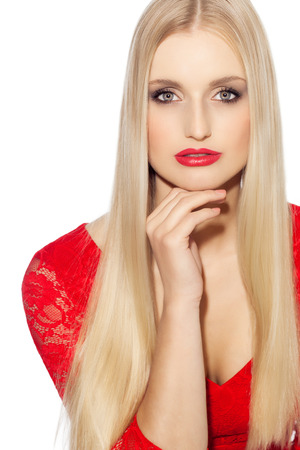 Studio portrait of beautiful Caucasian woman with blond hair. Woman wearing red lipstick and red lace dress.