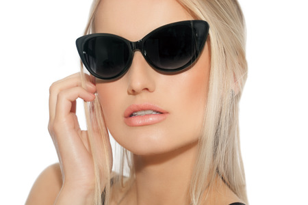 chic woman: Studio portrait of beautiful Caucasian woman with blond hair. Chic tanned woman with large sunglasses.