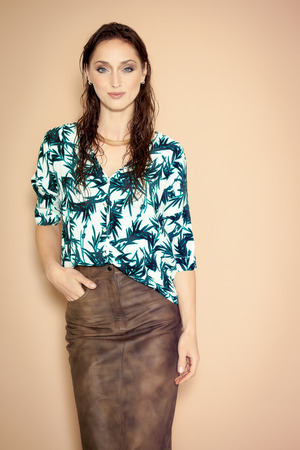 Fashion model wearing brown leather skirt and tropical blouse on beige background.