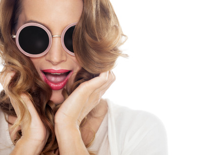 Happy excited woman closeup with beautiful hair wearing sunglasses over white background. Stock Photo