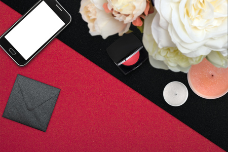 Top view scene with mobile phone, envelope and peonies over red and black background. Styled stock photography. Digital product mockup.