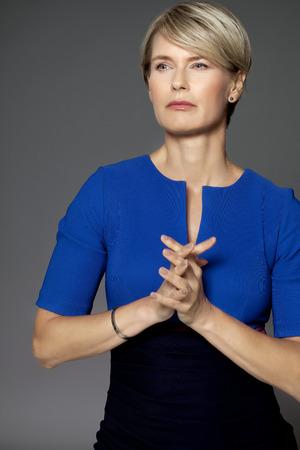mujer elegante: Mujer Seus con un vestido azul sobre fondo gris. Elegante mujer de cuarenta años de edad.
