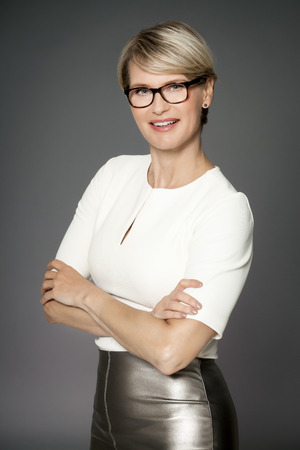 forty: Smiling business woman wearing reading glasses. Elegant forty year old woman.