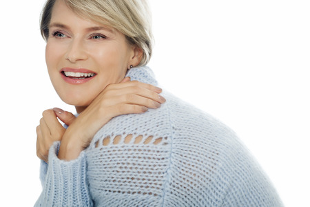 forty: Smiling cheerful woman posing in blue sweater vest over white background. Elegant forty year old woman.