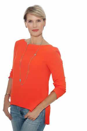 beautiful mature woman: Summer fashion model in jeans and orange tunic. Elegant forty year old woman. Stock Photo