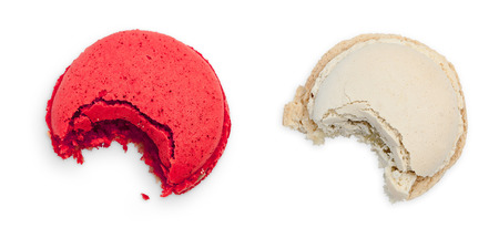tastes: Two bitten macarons, berry and vanilla taste. Top view isolated object on white background. Stock Photo