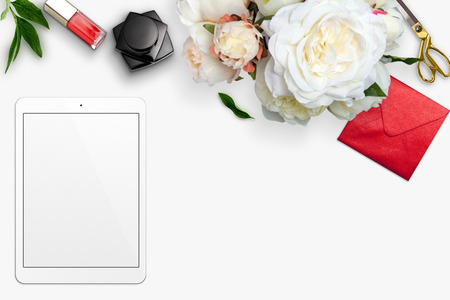 Top view scene with tablet, bouquet of peonies and stationery over white background. Styled stock photography. Digital product mockup.