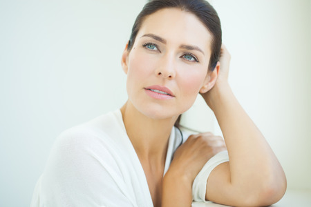 Belle femme assise à la fenêtre. bleu et blanc lumière lumière jour et high key. Banque d'images - 59851545