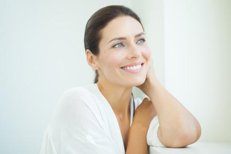 Mooie vrouw zit bij venster. Lichtblauw en wit daglicht en hoge drukken.