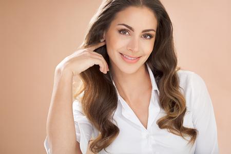 Glimlachende vrouw met lang bruin haar op beige achtergrond. Stockfoto