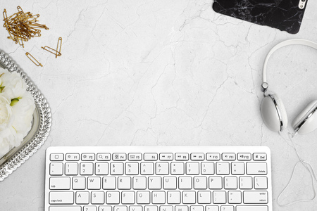 Elegant top view of desk with keyboard, mobile phone and headphones on marble. Styled stock top view mockup scene.