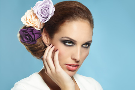 purple flower: Beautiful bridal visual of woman with three roses in hair on blue background.