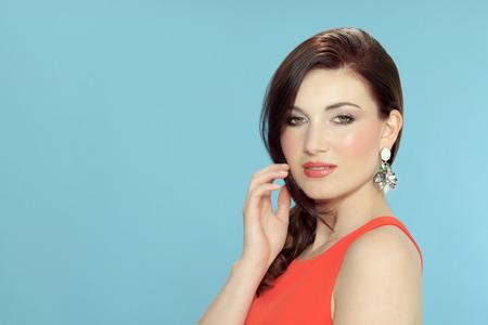Beautiful woman posing in orange dress and large statement earrings.
