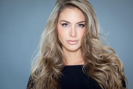 Jonge mooie vrouw met lang haar en highlights stellen in zwarte zijde kant top. Stockfoto