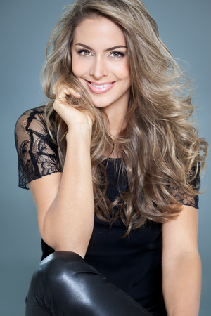 highlight: Young beautiful woman with long hair and highlights posing in black silk lace top. Smiling fashionable woman.