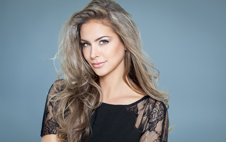 Young beautiful woman with long hair and highlights posing in black silk lace top. Smiling fashionable woman.
