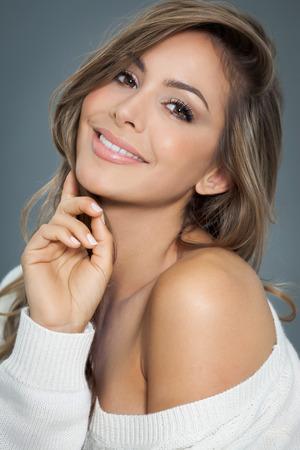 mujer elegante: Mujer hermosa joven con el pelo largo y pone de relieve que presenta en un suéter blanco. Sonriente mujer de moda.
