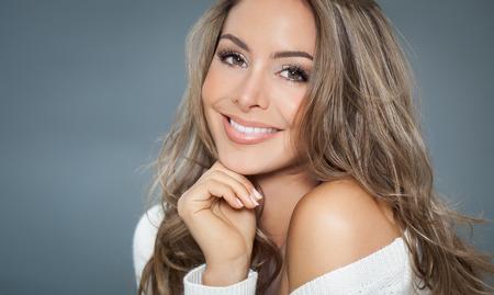 Jonge mooie vrouw met lang haar en belicht poserend in de witte trui. Lachende modieuze vrouw.