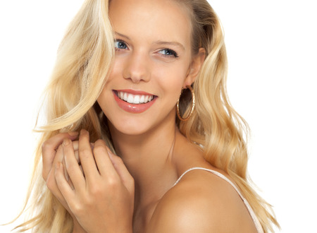 Beautiful smiling girl with long blond hair on beige background. Stock Photo