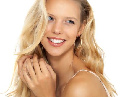 hair blond: Bella ragazza sorridente con lunghi capelli biondi su sfondo beige.