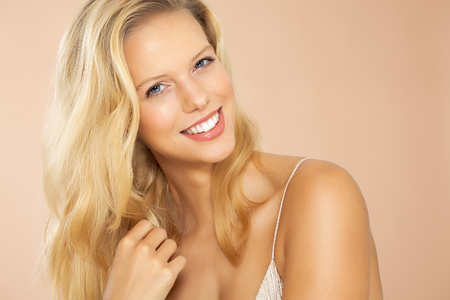 portrait studio: Beautiful smiling girl with long blond hair on beige background. Stock Photo