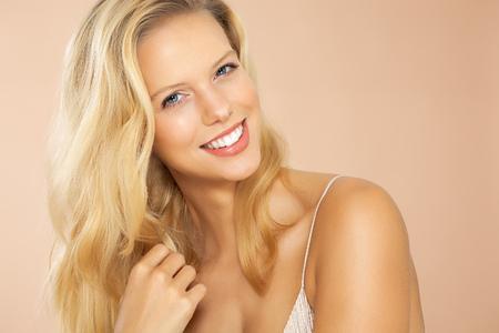 cabello rubio: Bella joven sonriente con el pelo rubio largo en el fondo de color beige. Foto de archivo