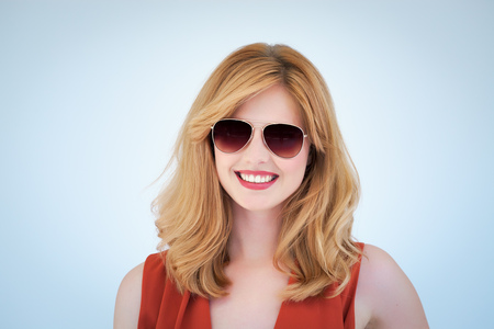 Young modern hip woman with blond hair wearing aviator sunglasses on blue background.