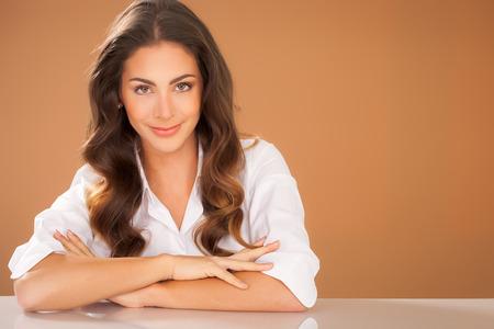 warm shirt: Beautiful European brunette woman with long hair wearing white shirt over beige warm background.