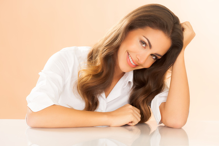 Beautiful European brunette woman with long hair wearing white shirt over beige warm background.