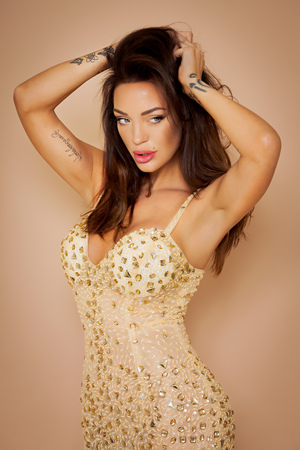 Golden toned portrait of woman with tatoos wearing sequin dress. Stock Photo
