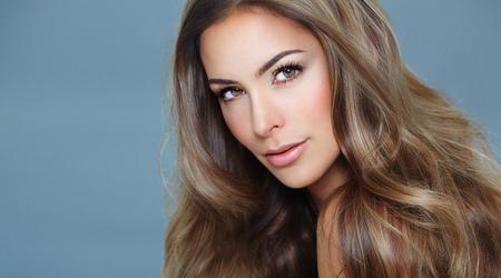 Jonge mooie vrouw met lang haar en highlights die zich voordeed op een blauwe achtergrond.