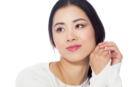 Beautiful casual young Asian woman portrait in white striped sweater on white background.