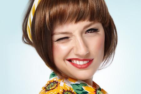 Funny wink retro sixties style girl closeup.