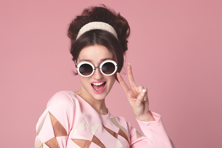 Funny sixties style girl with sunglasess on pink background. Banco de Imagens