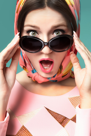 Smiling sixties style woman with scarf and sunglasses. Stock Photo