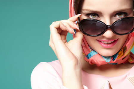 Smiling sixties style woman with scarf and sunglasses. Banco de Imagens