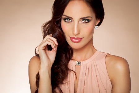 Beautiful elegant young woman with long brown styled hair and makeup.