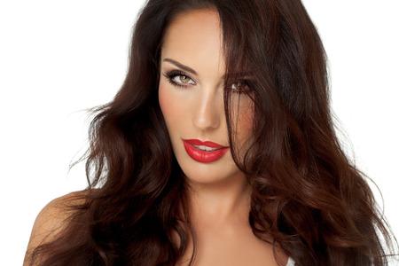 Hermosa mujer joven elegante con cabello largo estilo castaño y lápiz labial rojo sobre fondo blanco.