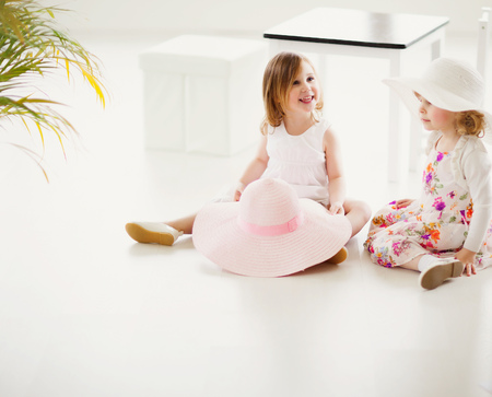 Two three year old girls playing with large hats in summer daylight studio.
