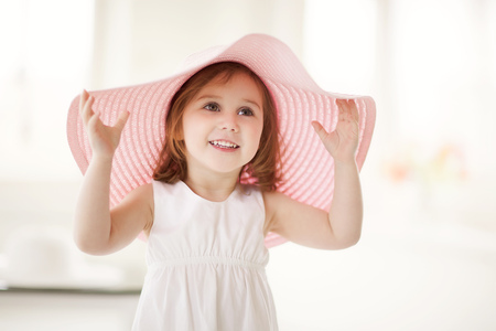 Little girl playing with large summer hat in daylight studio.