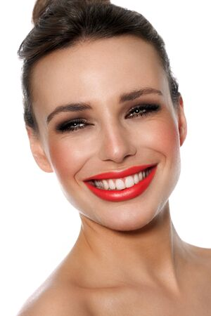 Young Caucasian woman with heterochromia wearing warm bright summer makeup over white background. Archivio Fotografico
