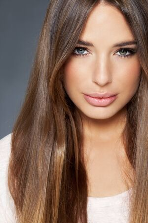 Young Caucasian woman with heterochromia and long blond hair, on grey studio background. Stock Photo