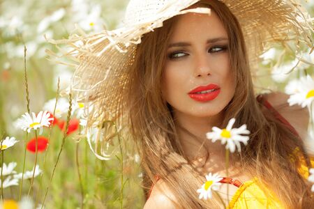 Portraits of young Caucasian woman outdoors in the sun wearing straw hat.