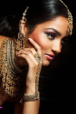 Young Indian woman wearing traditional jewelry and colorful makeup on black background.