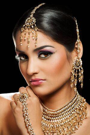 Junge indische Frau, die traditionellen Schmuck und buntes Make-up auf schwarzem Hintergrund trägt.
