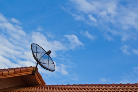 communication satellite dish over blue sky on roof