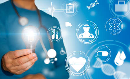 Doctor with stethoscope and light bulb in hand and medical symbols in concept of medical idea and prognosis