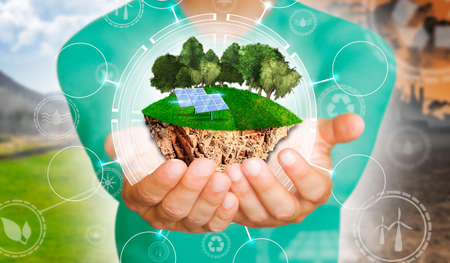 Hands of man holding an island with green grass, trees and solar panels in concept of environmental protection. Backdrop as a concept of energy efficiency.